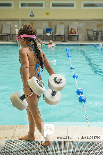 Girl carrying dumbbell-shaped floats by poolside