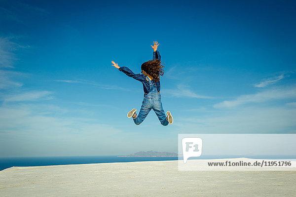 Girl in midair  sea and sky in background  Oía  Santorini  Kikladhes  Greece