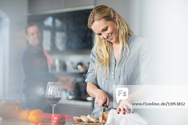 Frau schneidet Brot auf der Küchentheke