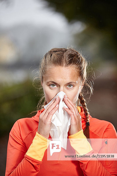 Young woman outdoors blowing her nose