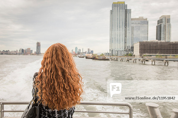 Rear view of long red haired businesswoman on ferry deck looking out at skyline  New York  USA