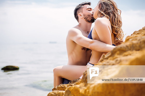 Couple kissing on rock