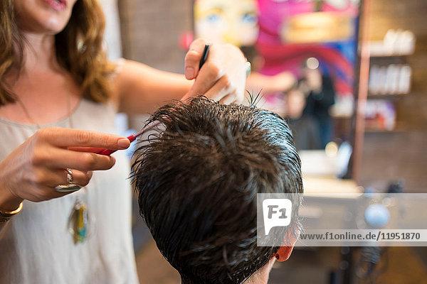 Im Salon arbeitende Friseurin