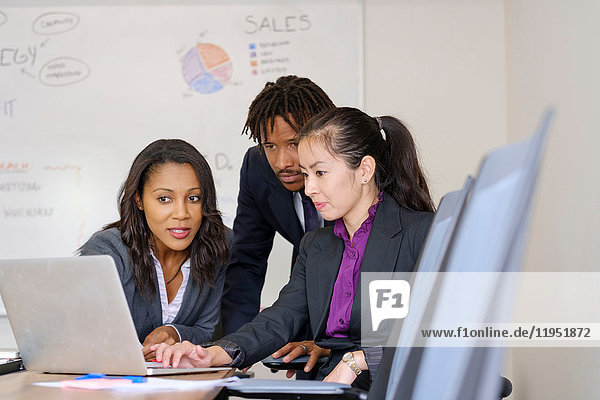 Businessman and businesswomen  in office  brainstorming  using laptop
