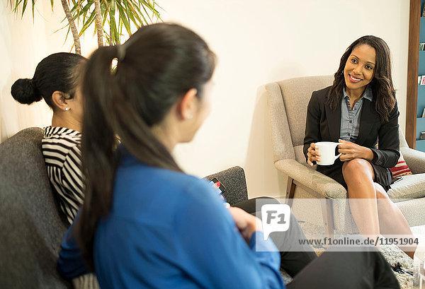 Three businesswomen sitting on office sofa  having relaxed meeting