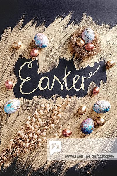 Draufsicht auf gefärbte und goldbemalte Ostereier mit handgeschriebenen Ostern