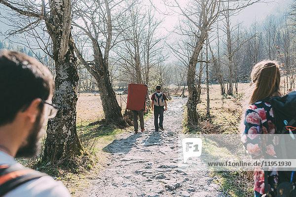 Rückansicht von erwachsenen Boulderfreunden auf einem Feldweg  Lombardei  Italien