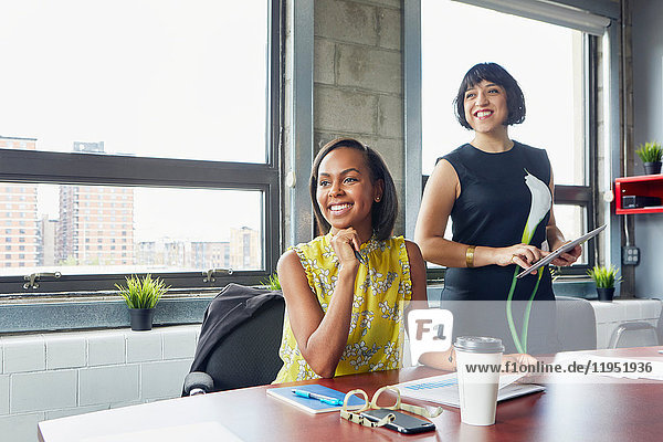 Zwei Frauen im Amt  wegschauen  lächeln