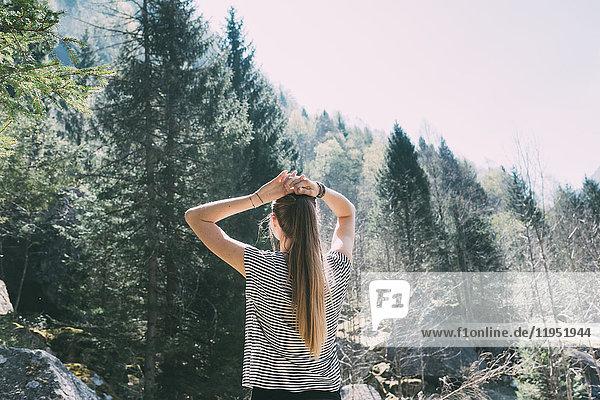 Rückansicht einer jungen Frau  die zum Wald aufschaut  Lombardei  Italien