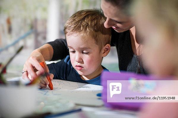 Lehrer unterrichtet Jungen zum Malen