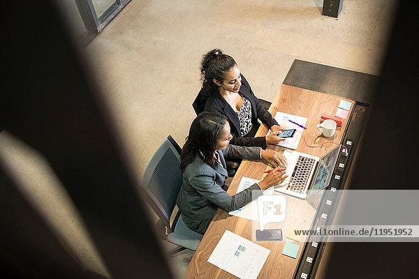 Zwei Geschäftsfrauen sitzen am Schreibtisch  verwenden einen Laptop  schauen auf ein Smartphone  erhöhte Ansicht