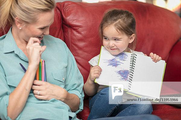 Tochter zeigt stolz Bleistiftzeichnungen der Mutter