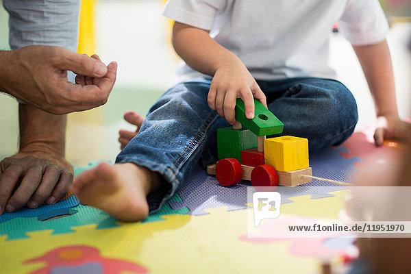 Lehrer und Junge spielen mit Spielzeugeisenbahn