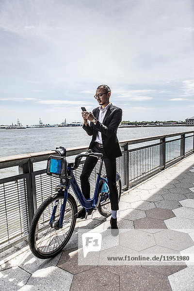 Mittelgroßer erwachsener Geschäftsmann auf dem Fahrrad schaut auf ein Smartphone entlang der Uferpromenade der Stadt