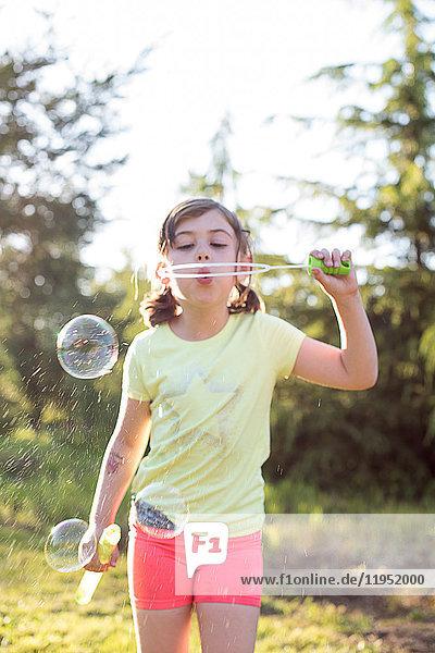 Junges Mädchen bläst draussen Seifenblasen