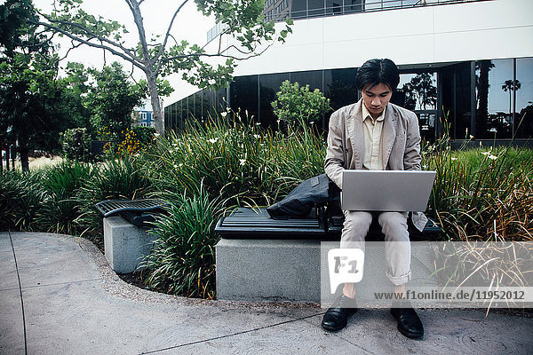 Young man sitting outdoors  using laptop