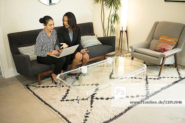 Zwei Businessfrauen sitzen auf einem Bürosofa  benutzen einen Laptop und schauen auf den Bildschirm