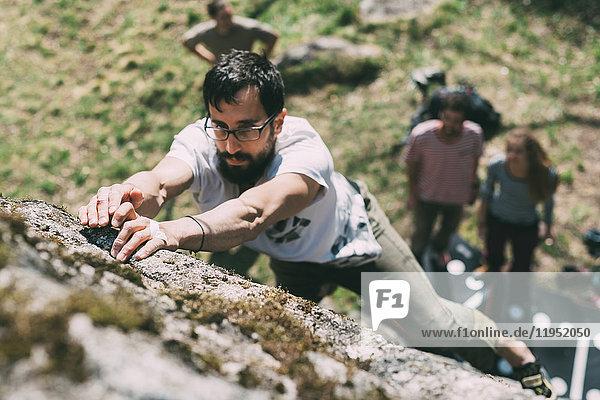 Freunde beobachten männliche Boulderer beim Bouldern  Lombardei  Italien