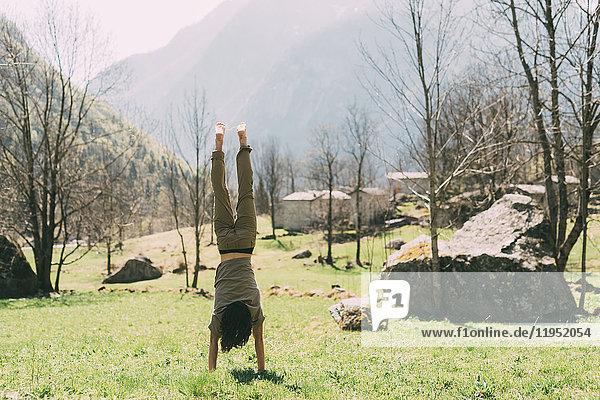 Rückansicht eines jungen männlichen Boulderers beim Handstand im Tal  Lombardei  Italien