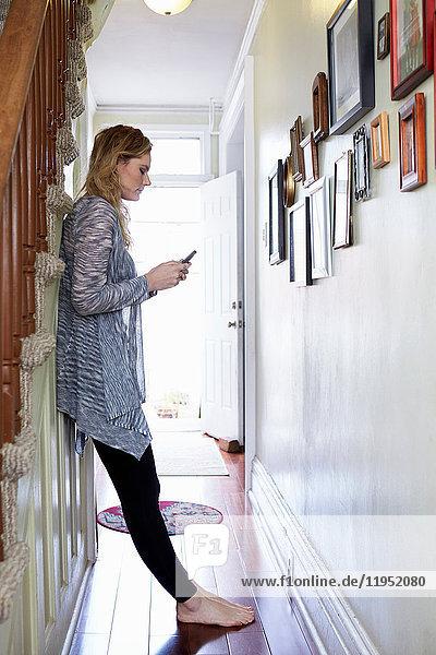 Frau benutzt Mobiltelefon auf dem Flur