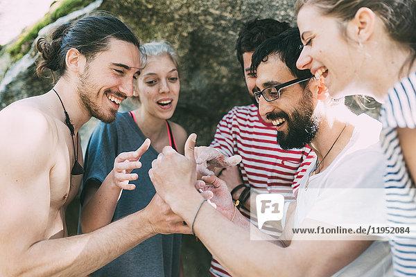 Fünf erwachsene Boulderfreunde schauen und lachen über Smartphone  Lombardei  Italien