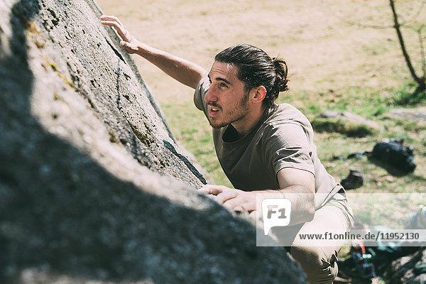 Junger männlicher Boulderer klettert einen Felsbrocken hoch  Lombardei  Italien
