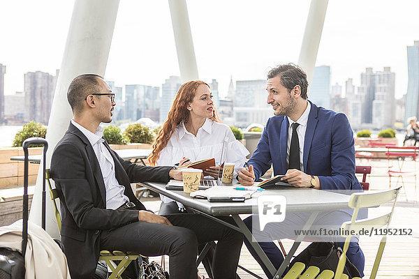 Geschäftsleute treffen sich im Hafencafé mit der Skyline von New York  USA