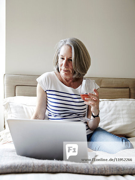 Senior woman with grey bob sitting on bed looking at laptop