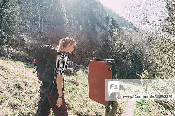 Erwachsene Freunde mit Bouldermatten-Rucksack wandern auf ländlichem Weg  Lombardei  Italien