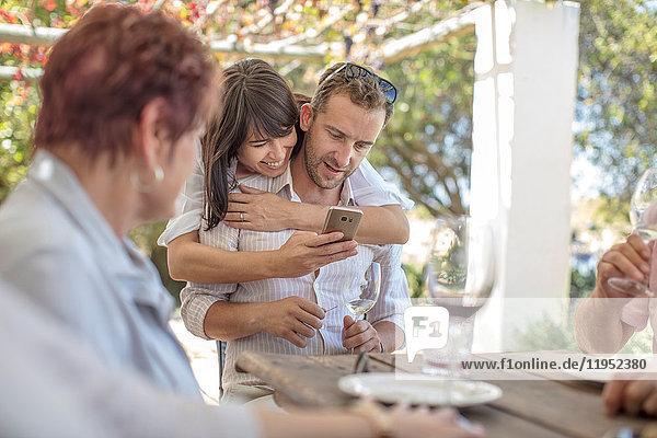 Familie beim Mittagessen im Freien unter Weinrebengittern