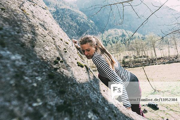 Junge weibliche Bouldererin beim Klettern am Boulder  Lombardei  Italien