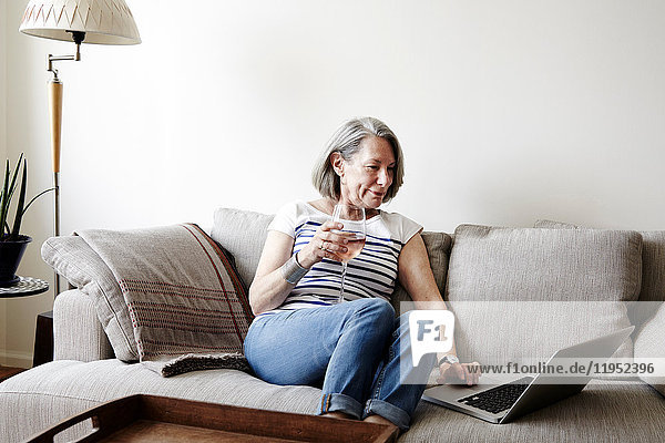 Senior woman with grey bob sitting on sofa looking at laptop