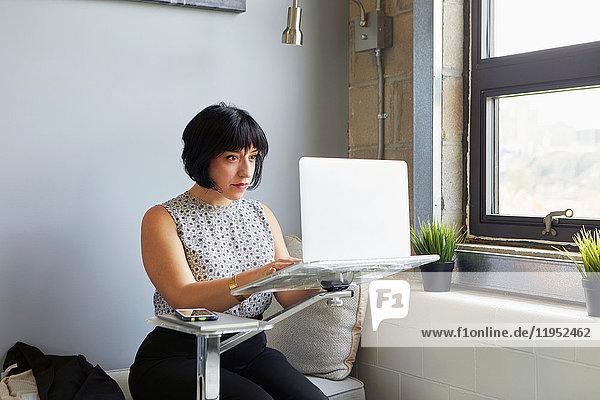 Frau sitzt mit Laptop auf Laptop-Ständer