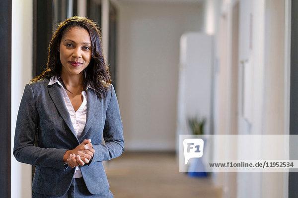 Porträt einer Geschäftsfrau im Büroflur  die Hände gefaltet  lächelnd