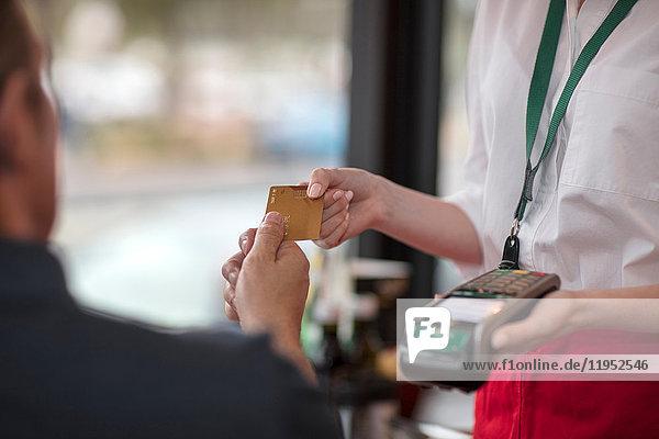 Kunde gibt Kreditkarte an Kellnerin zur Zahlung am Kartenautomaten ab