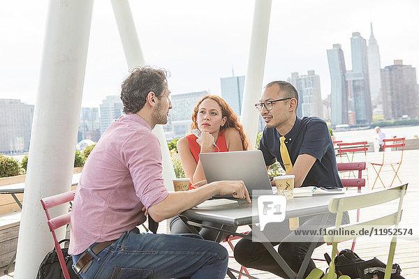 Geschäftsleute mit Laptop im Hafencafé  New York  USA