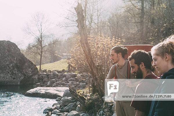 Drei erwachsene Freunde beim Bouldern mit Blick auf den Fluss  Lombardei  Italien