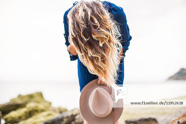 Mid adult woman in coastal setting  holding hat  bending over  hair covering face