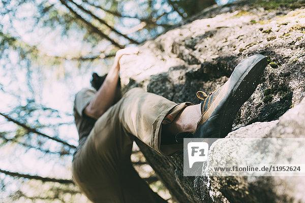 Niedrigwinkelansicht eines männlichen Boulderers beim Klettern von Felsbrocken  Lombardei  Italien