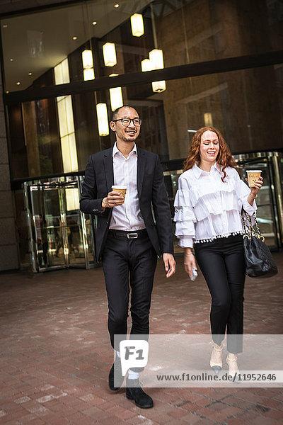 Junge Geschäftsfrau und Mann mit Kaffee zum Mitnehmen schlendern auf dem Bürgersteig  New York  USA