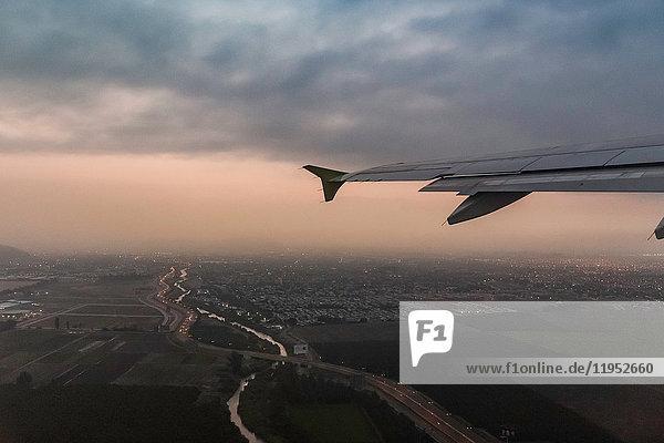 Flugzeugflügel und Luftaufnahme der Lichter der Stadt Punta Arenas in der Abenddämmerung  Region Magallanes  Chile