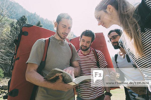 Erwachsene Boulderfreunde schauen im Reiseführer nach  Lombardei  Italien