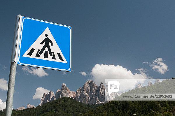 Schild für Fußgängerübergang über die Odle Mountains und den blauen Himmel  Tal von Funes  Dolomiten  Italien