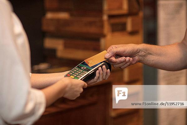 Ausschnittansicht eines Kunden  der kontaktlos bezahlt