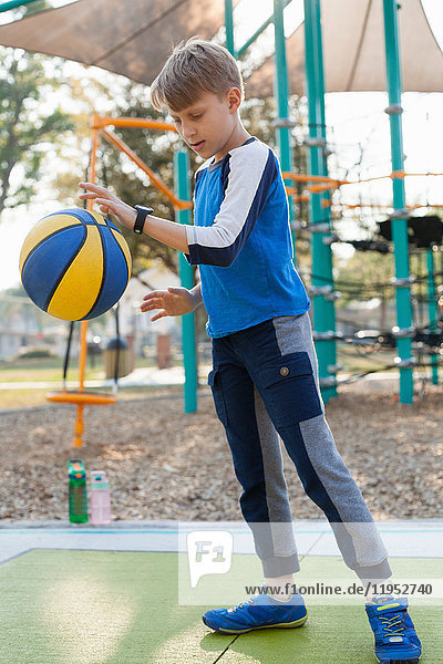 Junge hüpft Basketball auf dem Spielplatz