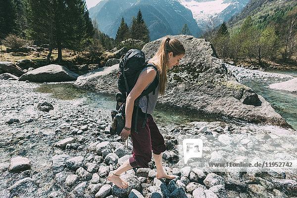 Barfüssiger weiblicher Boulderer tritt über Flusssteine  Lombardei  Italien