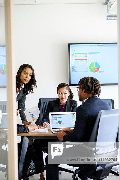 Geschäftsmann und Geschäftsfrauen  die im Büro sitzen  diskutieren  Daten betrachten