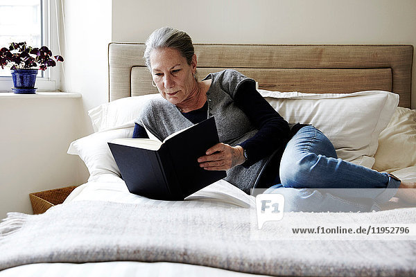 Senior woman with grey hair reclining on bed reading book