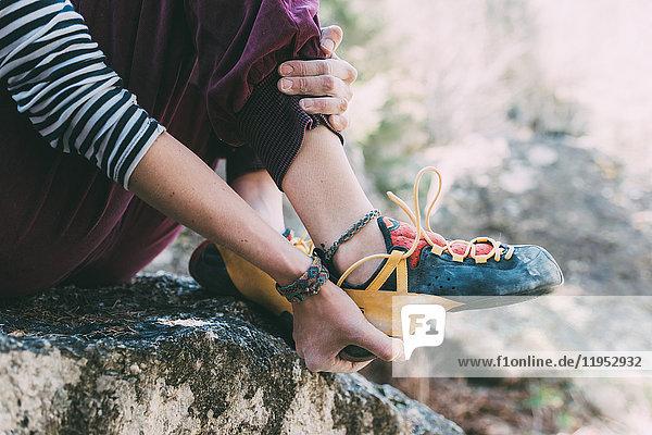 Taille eines weiblichen Boulderers  der einen Kletterschuh anzieht  Lombardei  Italien