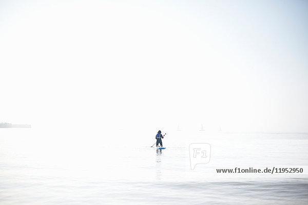 Fernblick einer Paddelboarderin  die auf nebliger See hinauspaddelt